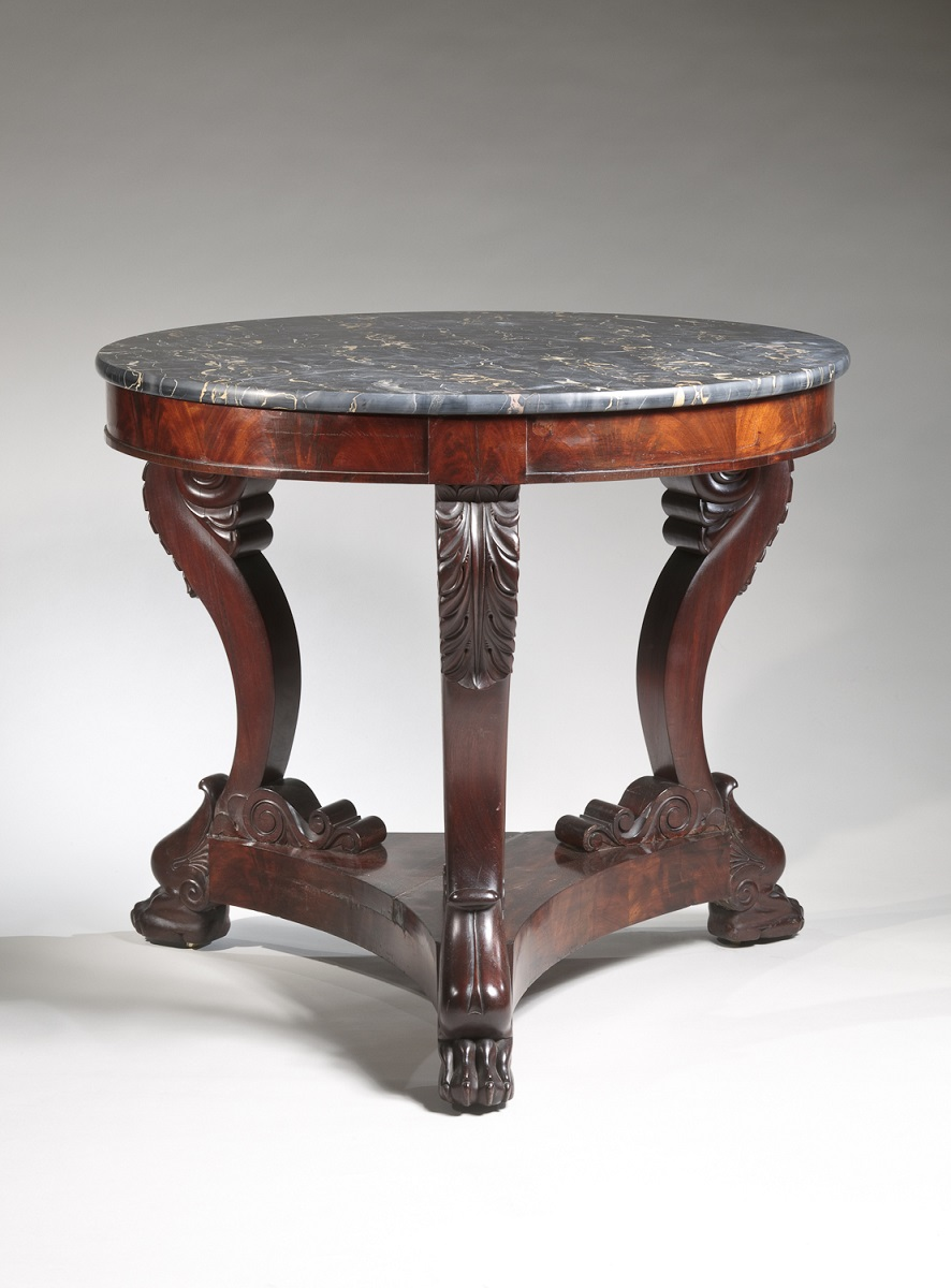 "Carved Mahogany Gueridon with Egyptian Marble Top Boston, c. 1830 The circular ""Egyptian"" marble top above a conforming skirt supported by three scrolled cabriole legs with acanthus carving at the knees, resting on a tripartite plinth raised on carved lion's paw feet with recessed casters. Secondary wood: chestnut. H: 30¾ Diameter: 34"""