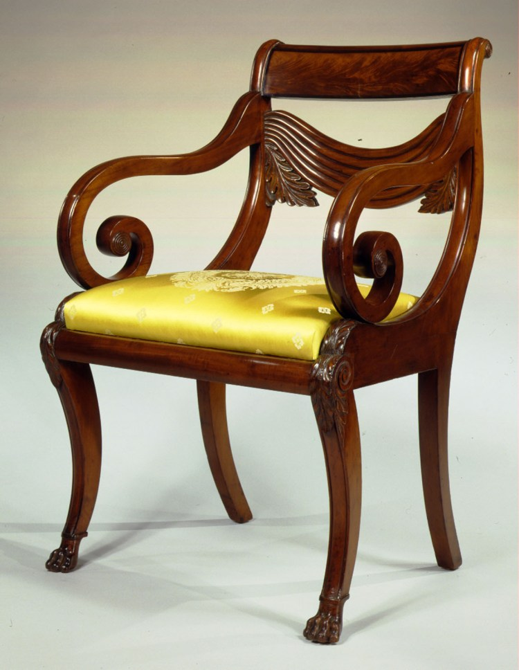 Monumental Carved Mahogany Klismos Armchair: The crest rail inlayed with flame mahogany and banded with rosewood above a carved stay rail simulating pleated, draped fabric flanked by acanthus leaves above an upholstered slip seat, all held between scrolled styles sweeping forward and resting on the seat rails terminating with acanthus carving above the knees, the arms attached to the styles just below the crest rail, scrolling forward and down to rest on the seat rails, the saber front legs carved with volutes and acanthus at the knees and terminating with carved dog paw feet, rear saber legs.