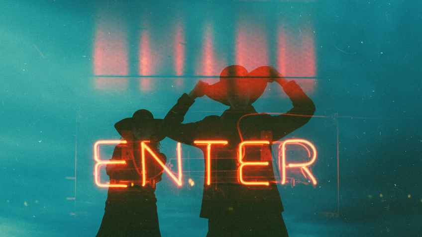 a neon signage with two person behind