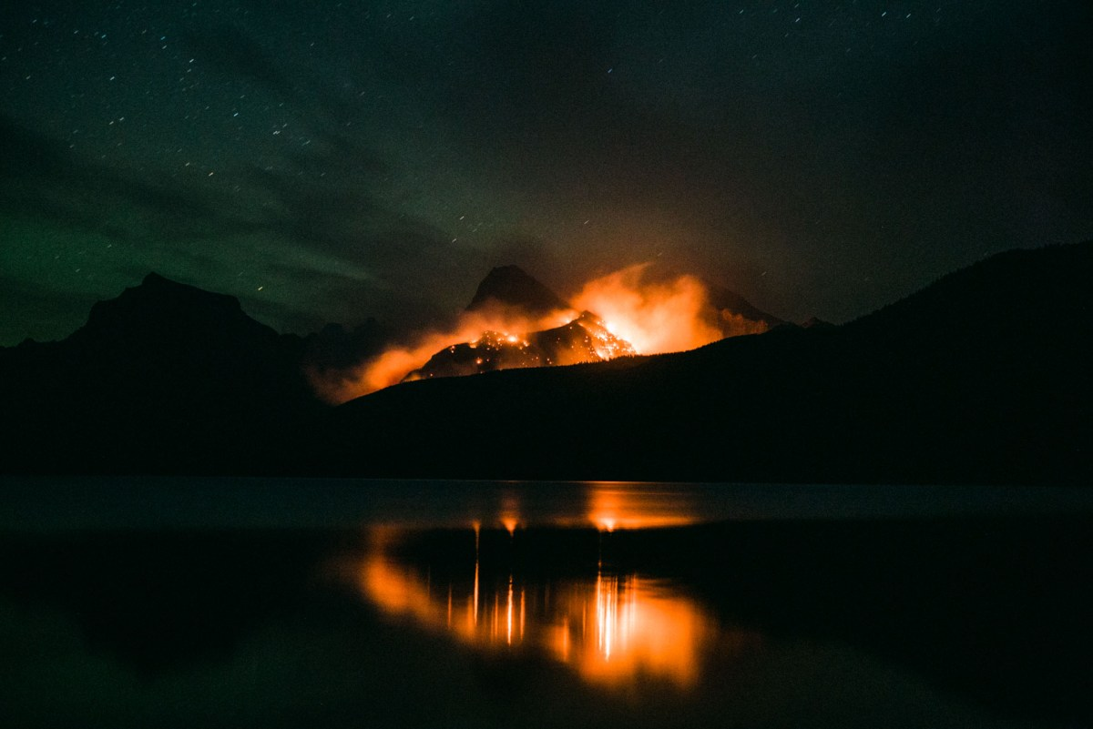 a wildfire seen across lake mcdonald in glacier national park