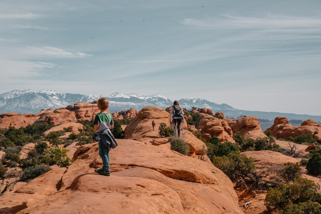 family with kids hiking in arches national park