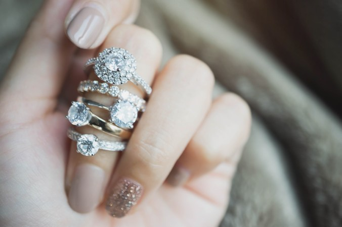 5 diamond rings on one woman's finger