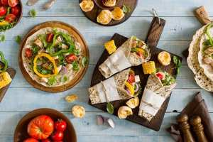 Roll tortilla with grilled chicken fillet on wooden cutting boar