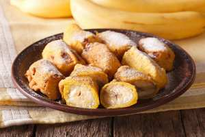 Traditional fried bananas sprinkled with powdered sugar close-up