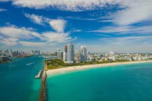 Drone aerial Miami Beach Florida highrises with clear blue waters and a blue sky