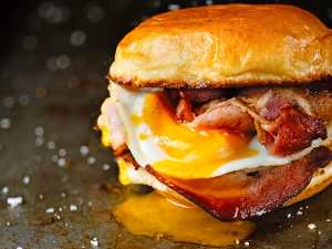 Rustic bacon egg breakfast sandwich bun on an industrial griddle