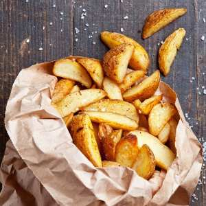 Potato wedges with salt on a wooden table
