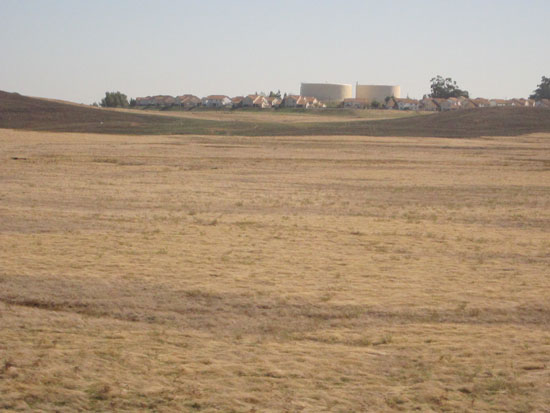 A field bounded by a subdivision & refineries (author photo)