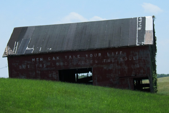 Photograph of decaying barn with religious message