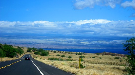 The road, the hills, the ocean make for a spectaular and colorful vista.