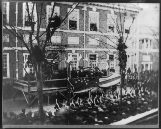 Lincoln stands on a platform with an enormous flag draped on the rail and before a crowd of spectators and an armed guard.