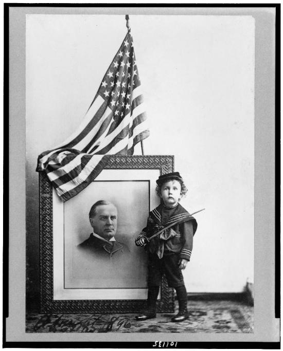 Boy in sailor uniform with flag-draped portrait of President McKinley (Courtesy of the Library of Congress).