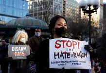 personas que sostienen pancartas durante una Vigilia por la Paz