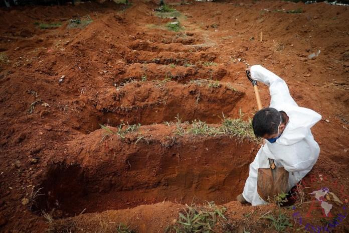 Un trabajador abre hoy fosas para enterrar víctimas mortales de covid-19