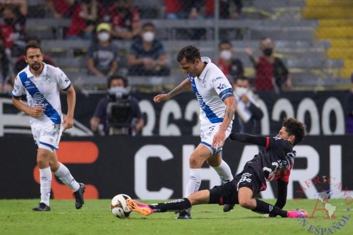 Jeremy Márquez (d) de Atlas disputa el balón con Maximiliano Perg (i) de Puebla