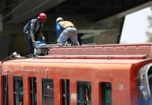Bomberos y operarios del área de emergencias trabajan para retirar uno de los vagones que colapsaron en la noche de este lunes, hoy, en Ciudad de México