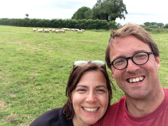 Two people in front of a field of sheep in Ireland