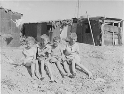 Children of migrant cotton field workers from Sweetwater, Oklahoma in front of their home near Casa Grande, AZ. May, 1937. Photo by Dorothea Lange