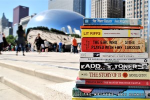 Stack of books in focus in the foreground, with Chicago's Cloud Gate in the background