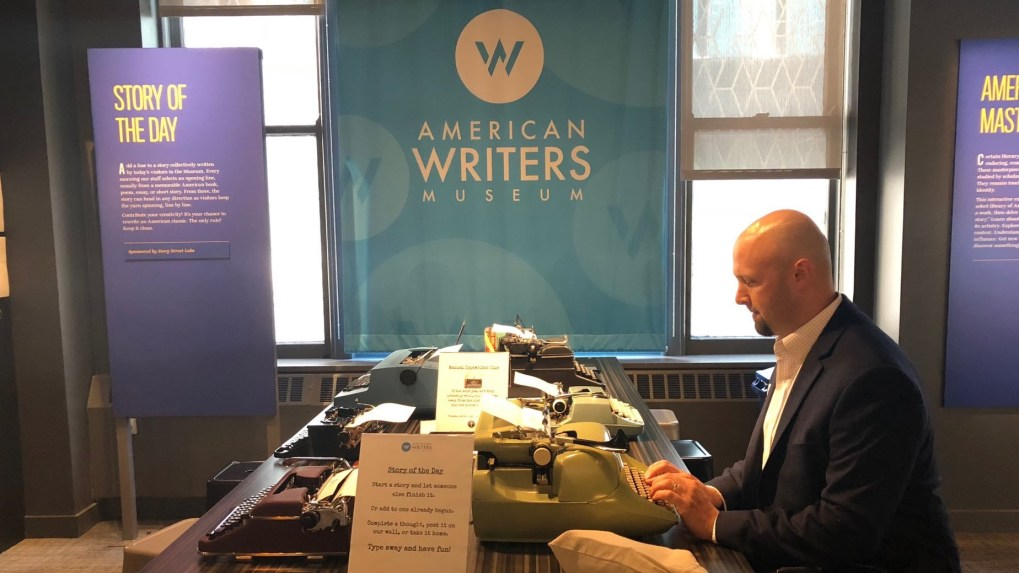 A man in a blazer uses typewriters at the American Writers Museum