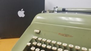 Royal typewriter next to a typewriter case with a sticker of the Apple logo on it