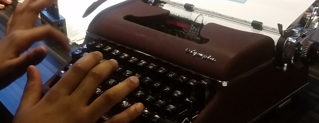 girl's hands typing on a typewriter