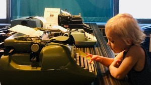 small child typing on a green typewriter at the Story of the Day exhibit