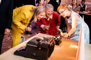 Two guests and a staff member admiring a typewriter at the American Writers Museum Annual Benefit in Chicago