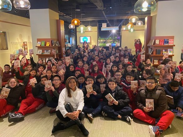 Writer and activist Julissa Arce sitting on the floor with a large group of school children following a program at the American Writers Museum in Chicago, IL