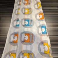 A white scarf with a design yellow, orange, and blue typewriters in grey circles. Thin, somewhat sheer material.