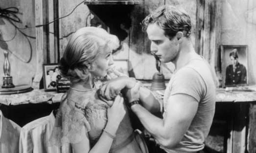 A black and white snapshot from the film of Marlon Brando and Vivien Leigh sharing a tense moment. Brando is gripping Leigh's wrist as she stares at him with wide eyes.