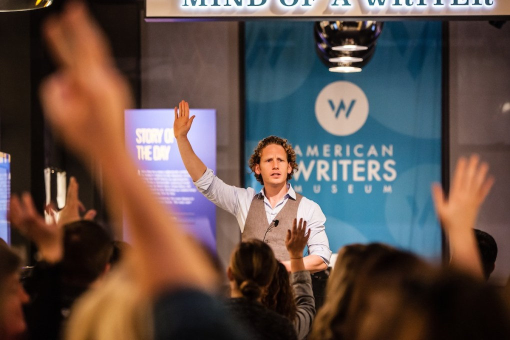A man raising his hand while giving a presentation at the American Writers Museum