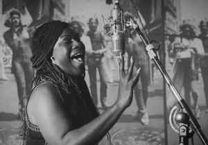 Black and white photo of Shea Diamond singing at a microphone