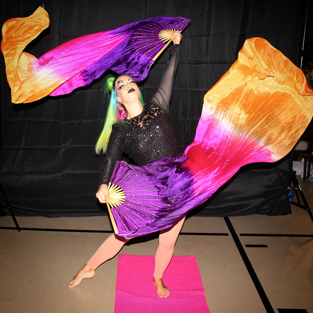 performer in black costume performing flow arts with purple, pink and gold fans