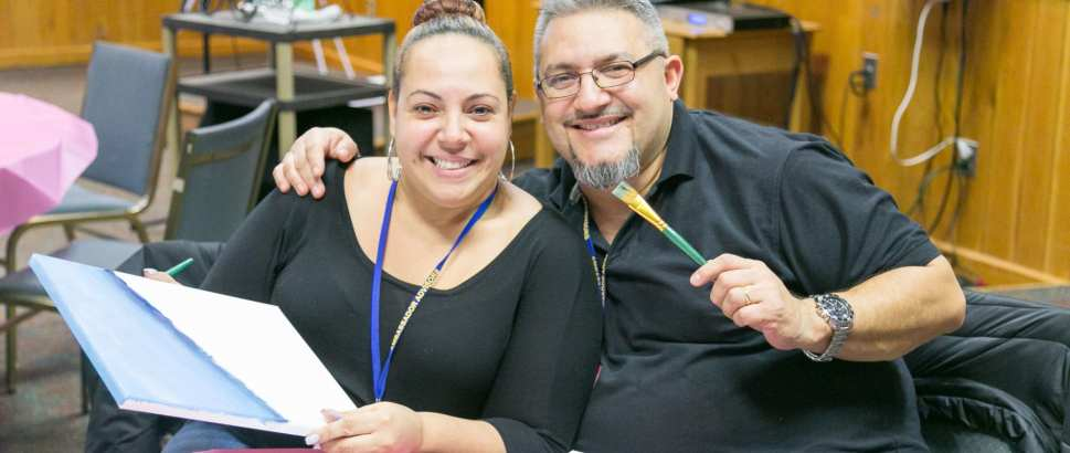 Man with arm around woman smiling and doing crafts