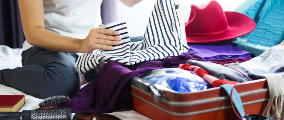 Travel and vacation concept, happiness young woman packing a lot of her clothes and stuff into suitcase on bed prepare for travel and journey trip in holiday.