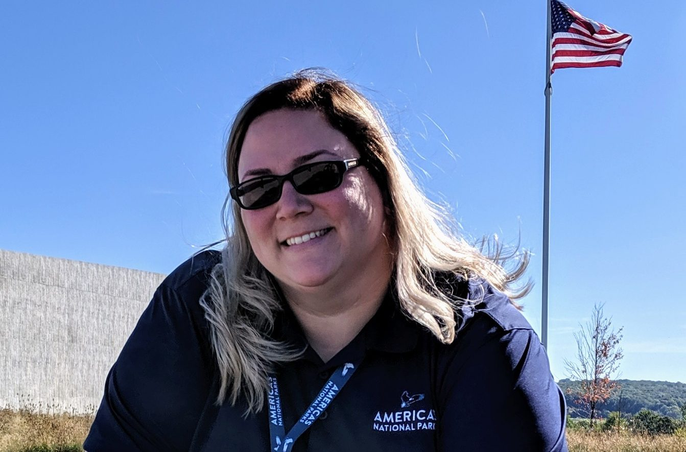 photo of Chastity H., wearing sunglasses, outside at Flight 93 National Memorial. American flag is visible flying in the background.