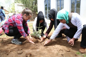 Bridget (left) works alongside her students to plant a tree at the Azrou Center.