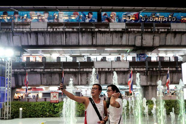 Tourists take a selfie at a department store in Bangkok on Wednesday. (Reuters photo)