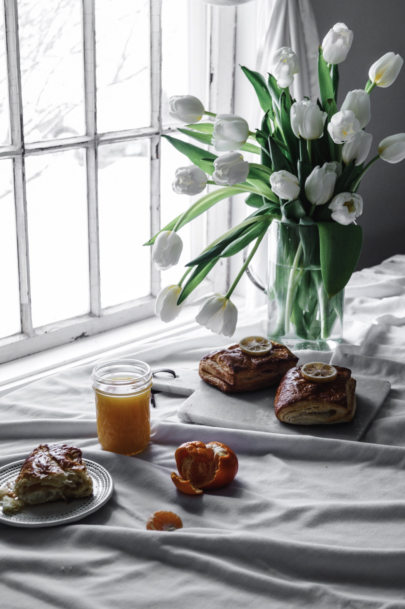 Super bright lemony filling tucked neatly inside the most delicious crispy-flaky Danish pastry. An early spring picnic, a flower bouquet of white tulips,  a wild story about boys and the perfect early spring brunch by A Messy Bun Kitchen