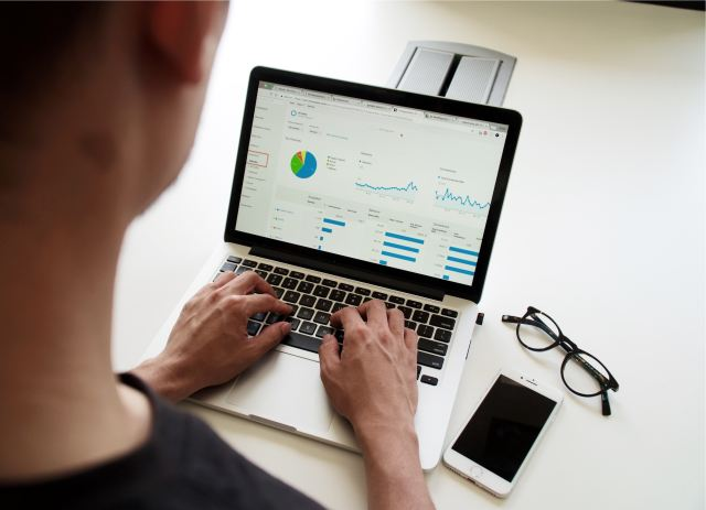 Photo of a perosn on the computer looking at google analytics for On Page SEO