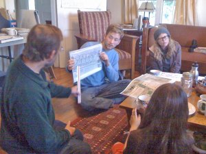 Photo of group of people sitting on the floor discussing a garden layout