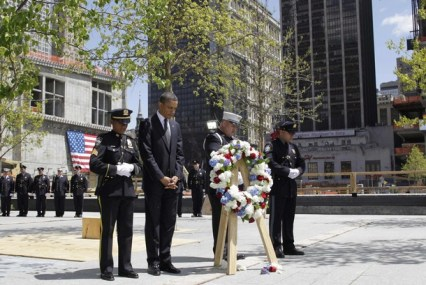 U.S. President Obama stands for a moment of silence with New York City police officers and firefighters after placing a wreath at Ground Zero
