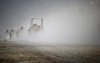 U.S. Mine Resistant Ambush Protected (MRAP) vehicles drive through Camp Adder before departing what is now known as Imam Ali Base near Nasiriyah, Iraq