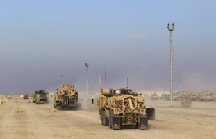 Vehicles move into formation while waiting at a staging area in Camp Adder to be part of the last U.S. military convoy to leave the country near Nasiriyah