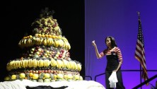 """U.S. First Lady Michelle Obama looks at a huge birthday cake made of fruits during an event to promote her """"Let's Move"""" initiative in Des Moines"""