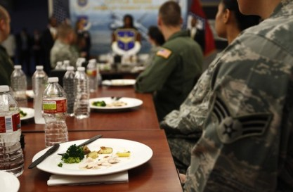 Plates sit in front of airmen as U.S. First Lady Michelle Obama speaks in a dining facility at Little Rock Air Force Base in Arkansas