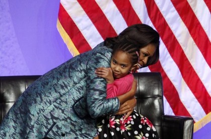 First lady Michelle Obama hugs a child after she presented a donation at the ground breaking ceremony for the Smithsonian National Museum of African American History and Culture in Washington