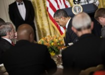 US President Barack Obama bows his head