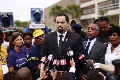 Benjamin Jealous, President of the NAACP speaks in front of Reverend Al Sharpton before a march and rally to the front of the Sanford Police Department in Florida